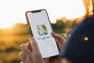 BERLIN, GERMANY JULY 2019: Hand Holding Smartphone with Google Maps application o. Google Maps is a service that provides information about geographical regions and sites around the world.